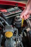 Mecánico de coche en servicio de reparación auto que comprueba el aceite Imagen de archivo