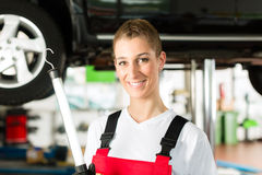 Mecánico de coche maduro del hombre y de la hembra en taller Imagen de archivo libre de regalías
