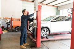Mecánico de coche Operating Hydraulic Lift en el taller de reparaciones fotografía de archivo