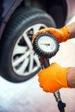 Mecánico de coche que comprueba la presión de neumático Fotos de archivo libres de regalías
