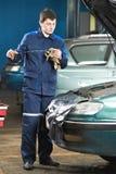 Mecánico de coche que revisa el nivel de aceite de motor Fotos de archivo libres de regalías