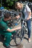 Mecánico de la bicicleta en tienda de la bici que consulta a un cliente Foto de archivo