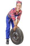 Mecánico de la mujer joven con una rueda de coche Imagen de archivo