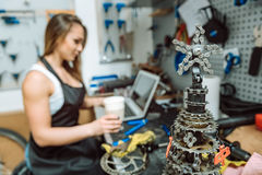 Mecánico de sexo femenino concentrado que tiene resto en el taller de reparaciones Foto de archivo libre de regalías