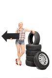 Mecánico de sexo femenino sosteniendo una flecha que señala a la izquierda Foto de archivo