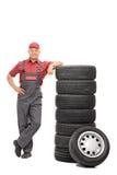 Mecánico de sexo masculino hermoso que se inclina en una pila de neumáticos fotos de archivo