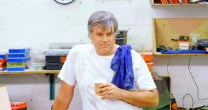 Mecánico de sexo masculino que come café en el garaje 4k almacen de video