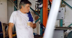 Mecánico de sexo masculino que come café en el garaje 4k almacen de metraje de vídeo
