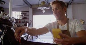 Mecánico de sexo masculino que comprueba la batería de moto en el garaje 4k de la reparación metrajes