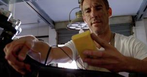 Mecánico de sexo masculino que comprueba la batería de moto en el garaje 4k de la reparación almacen de video