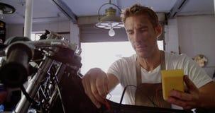 Mecánico de sexo masculino que comprueba la batería de moto en el garaje 4k de la reparación almacen de metraje de vídeo