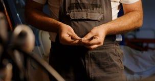 Mecánico de sexo masculino que comprueba a la llave inglesa en el garaje 4k metrajes