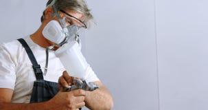 Mecánico de sexo masculino que comprueba la pintura de espray 4k almacen de metraje de vídeo