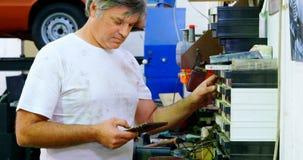 Mecánico de sexo masculino que comprueba recambios mientras que usa la tableta digital 4k almacen de metraje de vídeo