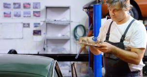 Mecánico de sexo masculino que comprueba un coche 4k metrajes