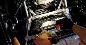 Mecánico de sexo masculino que mantiene un coche en el garaje 4k almacen de metraje de vídeo