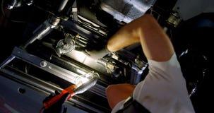 Mecánico de sexo masculino que mantiene un coche en el garaje 4k almacen de video