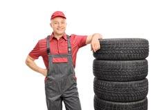 Mecánico de sexo masculino que se inclina en una pila de neumáticos imagen de archivo
