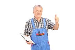 Mecánico de sexo masculino que sostiene el tablero y que da el pulgar para arriba imagen de archivo