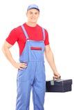 Mecánico de sexo masculino que sostiene una caja de herramientas foto de archivo libre de regalías