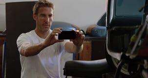 Mecánico de sexo masculino que toma la foto de la moto en el garaje 4k de la reparación almacen de metraje de vídeo