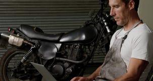 Mecánico de sexo masculino que usa el ordenador portátil en el garaje 4k de la reparación de la moto almacen de metraje de vídeo