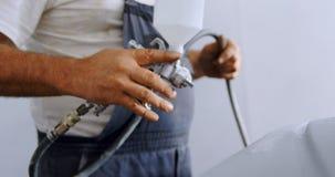 Mecánico de sexo masculino que usa la pintura de espray en el garaje 4k metrajes
