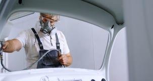 Mecánico de sexo masculino que usa la pintura de espray 4k almacen de metraje de vídeo