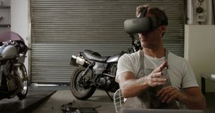 Mecánico de sexo masculino que usa las auriculares de la realidad virtual en el garaje 4k de la reparación de la moto almacen de metraje de vídeo