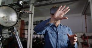 Mecánico de sexo masculino que usa las auriculares de la realidad virtual en el garaje 4k de la reparación de la moto metrajes