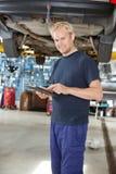 Mecánico de Yong con la tablilla digital Imagen de archivo