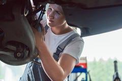 Mecánico dedicado que trabaja en un taller de reparaciones del automóvil moderno foto de archivo libre de regalías