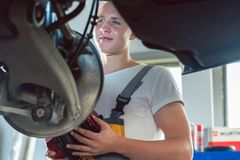 Mecánico dedicado que trabaja en un taller de reparaciones del automóvil moderno fotos de archivo libres de regalías