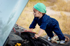 Mecánico del niño pequeño que repara el coche imagen de archivo libre de regalías