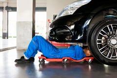 Mecánico en acostarse uniforme del azul y el trabajo debajo del coche en el aut foto de archivo