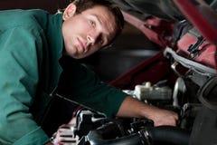 Mecánico en el automóvil de fijación del trabajo en servicio auto Fotografía de archivo libre de regalías
