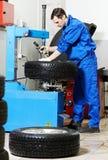 Mecánico en el cambiador auto del neumático de rueda Foto de archivo