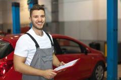 Mecánico en el taller de reparaciones auto que sostiene un tablero Foto de archivo