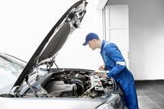 Mecánico europeo que examina un coche con la tableta Foto de archivo libre de regalías