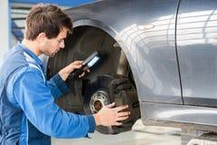 Mecánico Examining Brake Disc del coche en garaje Fotos de archivo