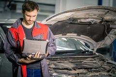 Mecánico Examining Car Engine con la ayuda del ordenador portátil fotos de archivo
