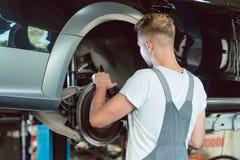 Mecánico experimentado que substituye los frenos de disco de un coche en una MOD foto de archivo