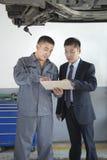 Mecánico Explaining al hombre de negocios, mostrándole el Bill Foto de archivo