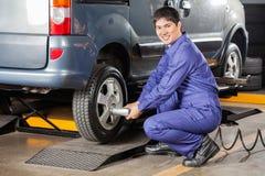 Mecánico feliz Fixing Car Tire en el taller de reparaciones fotos de archivo