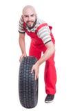 Mecánico feliz que empuja y que rueda una rueda de coche Fotos de archivo libres de regalías