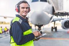 Mecánico feliz que tiene trabajo en aeródromo Imágenes de archivo libres de regalías