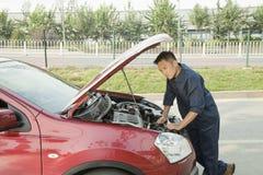 Mecánico Fixing Car por el borde de la carretera Imágenes de archivo libres de regalías