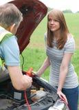 Mecánico Helping Female Motorist con la batería plana foto de archivo libre de regalías