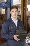 Mecánico Holding Car Battery del aprendiz en taller de reparaciones auto Foto de archivo libre de regalías