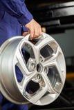 Mecánico Holding Metallic Alloy en el taller de reparaciones Imagenes de archivo